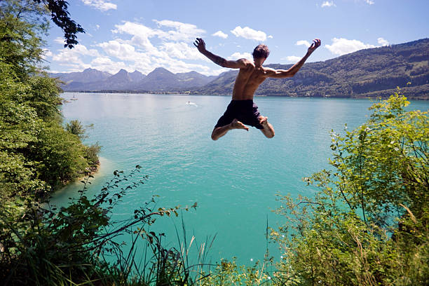 Young man jumping into blue water on a sunny day Young man leaps from a cliff into a blue Alpine lake below on a hot summer day.  davelongmedia stock pictures, royalty-free photos & images
