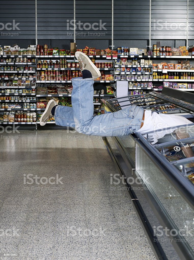 Young man jumping into refrigerator.  foto stock royalty-free