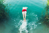 istock Young man jumping into the turquoise lake during summertime 1255209737