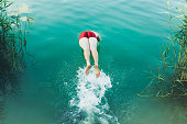 istock Young man jumping into the turquoise lake during summertime 1255209845