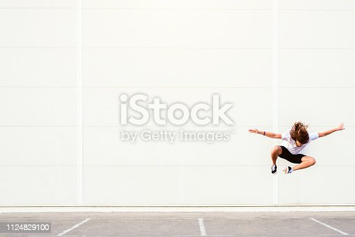 istock Young man jumping mid air 1124829100