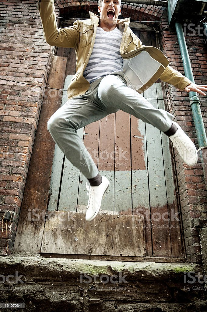 Young man jumping off a building royalty-free stock photo