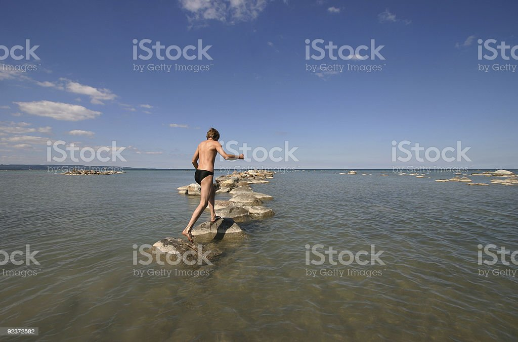 Young man jumping on beach stones royalty-free stock photo