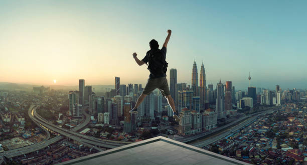 Young man jumping on rooftop stock photo