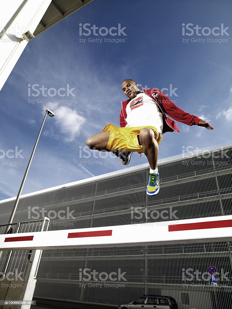 Young man jumping over barrier on street, low angle view foto de stock royalty-free