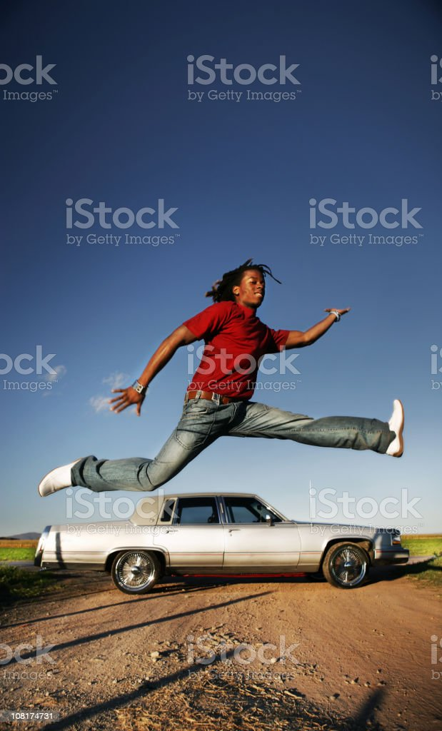 Young Man Jumping Over Car stock photo