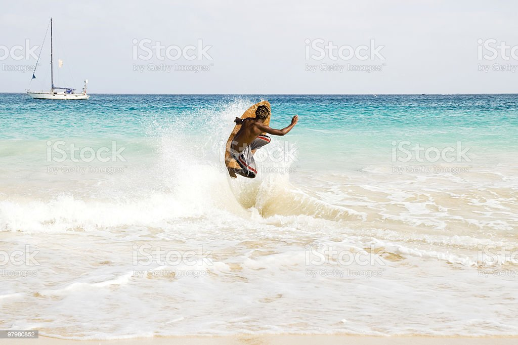Young man jumping wave on skimmer board stock photo