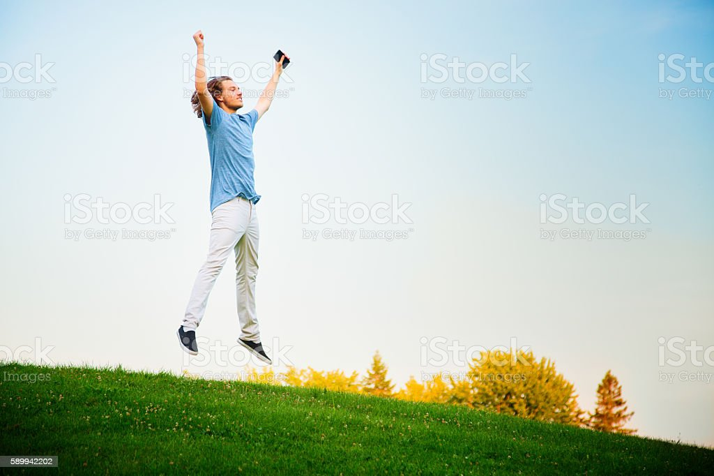 Young man jumping with joy after winning mobile AR game stock photo