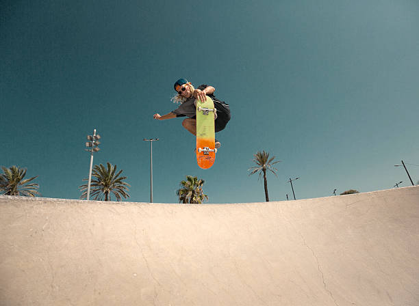 young man jumping with skateboard - skateboarding stock pictures, royalty-free photos & images
