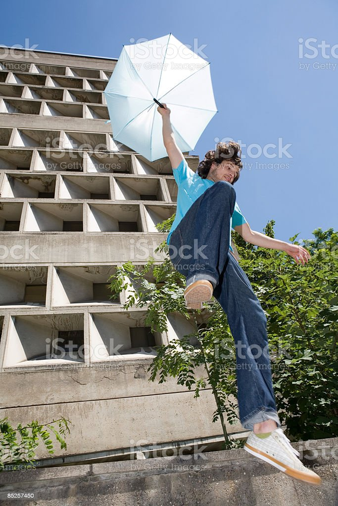 Young man jumping with umbrella royalty-free stock photo