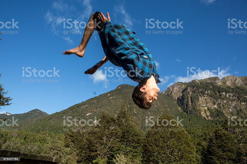 Young man jumps mid-air against blue sky stock photo