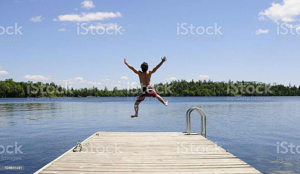 Young man jumps off dock on beautiful summer's day. stock photo