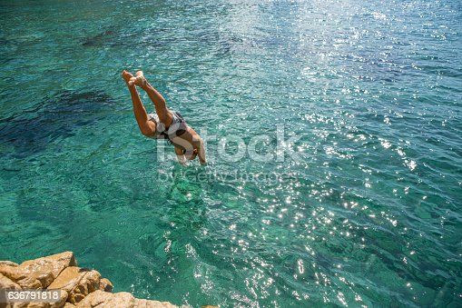 Young man jumps off the cliff into the sea, beautiful summer day in Sardinia, Italy.