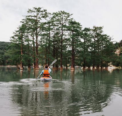 istock Young man kayaking on lake 828562552