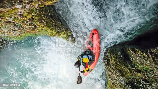 Elevated view of young man kayaking on waterfall.