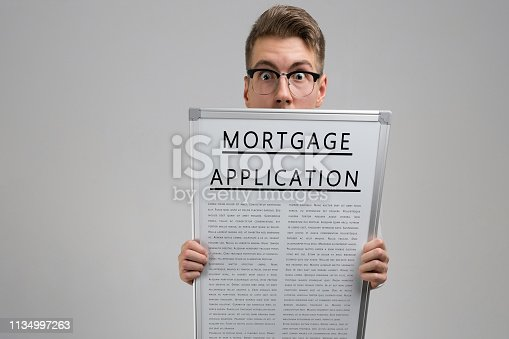 istock Young man keeps in front of him poster with mortgage application isolated on light background 1134997263