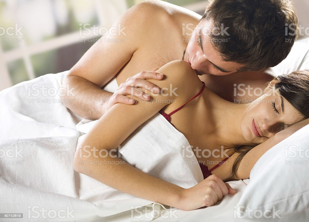 A young man kissing a woman on the shoulder while in bed stock photo