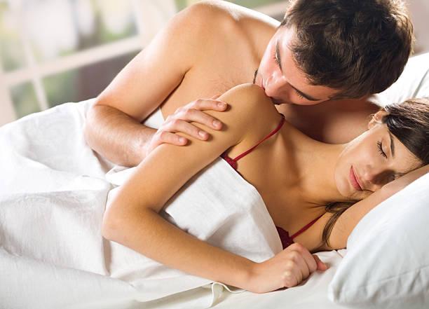 junge und attraktive glückliches paar umarmen im schlafzimmer - tantra massage stock-fotos und bilder