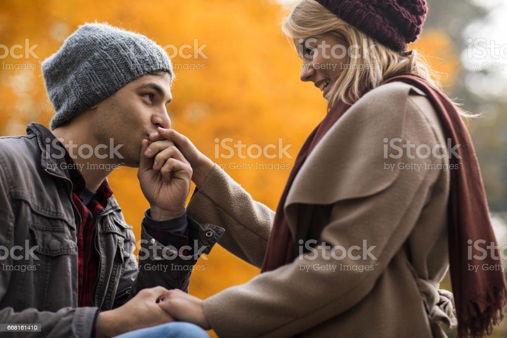 Hombre joven de la mano de novia besos en la naturaleza durante el otoño. - foto de stock
