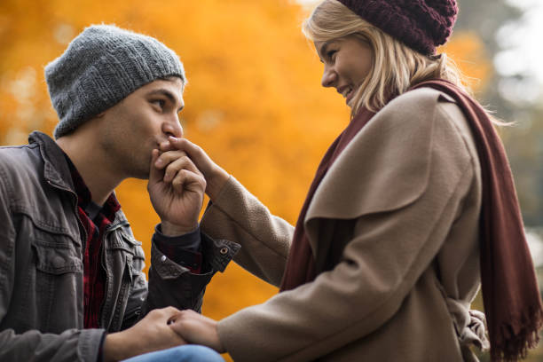 Young man kissing girlfriend's hand in in nature during autumn. Young man in love enjoying in autumn park with his girlfriend and kissing her hand. kissinghand stock pictures, royalty-free photos & images