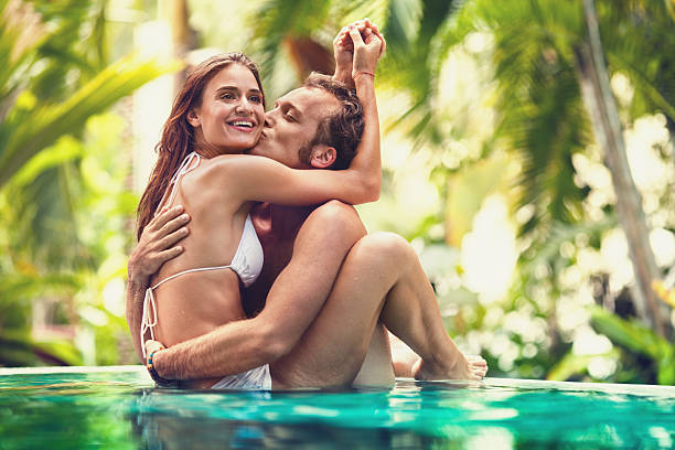 young man kissing hid girlfriend in infinity pool. - couple lap stock photos and pictures