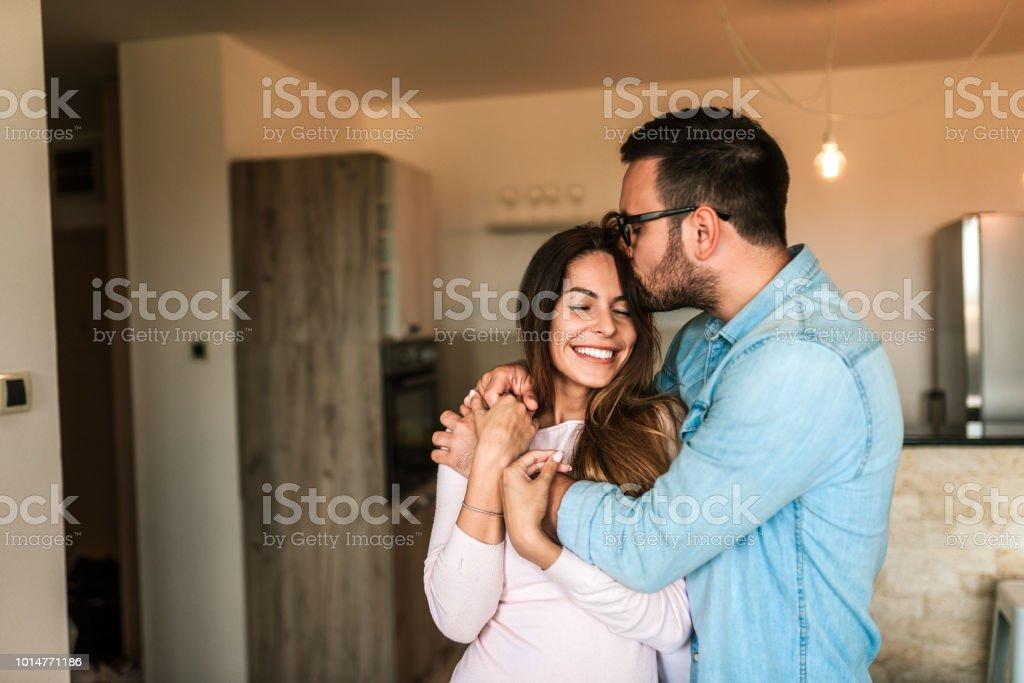 Hombre joven besar a su esposa en la frente en el interior. - foto de stock