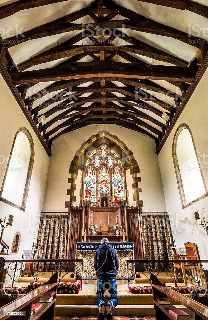 Jovem ajoelhado no altar da igreja - foto de acervo