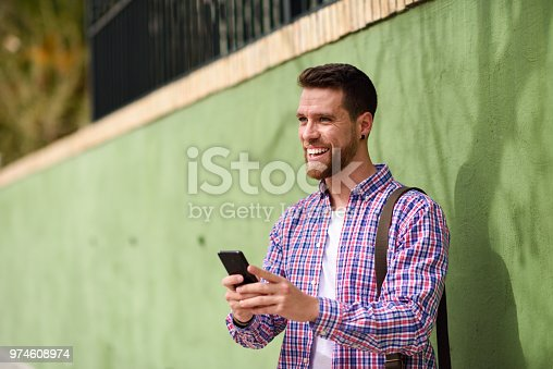 Young man laughing with his smart phone in urban background. Guy wearing casual clothes. Lifestyle concept.