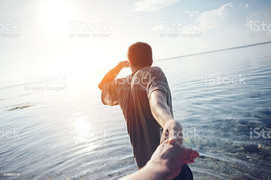 Young man leading woman stock photo