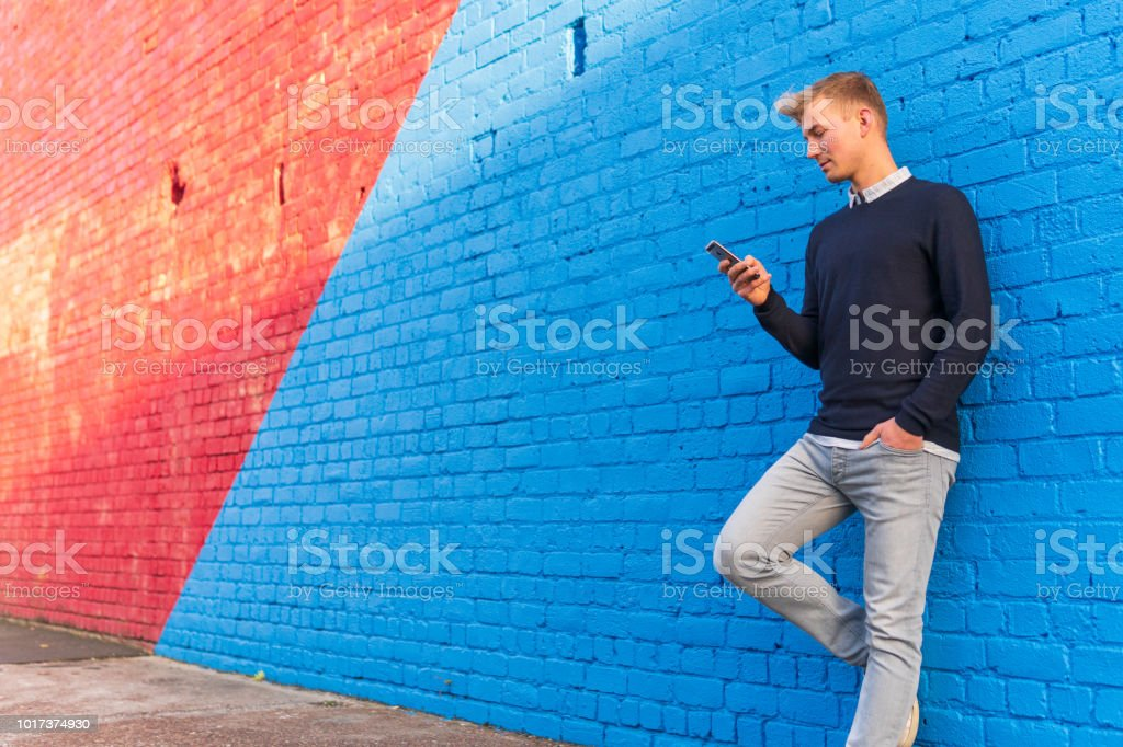 Young man leaning against a brick wall while using a smart phone stock photo