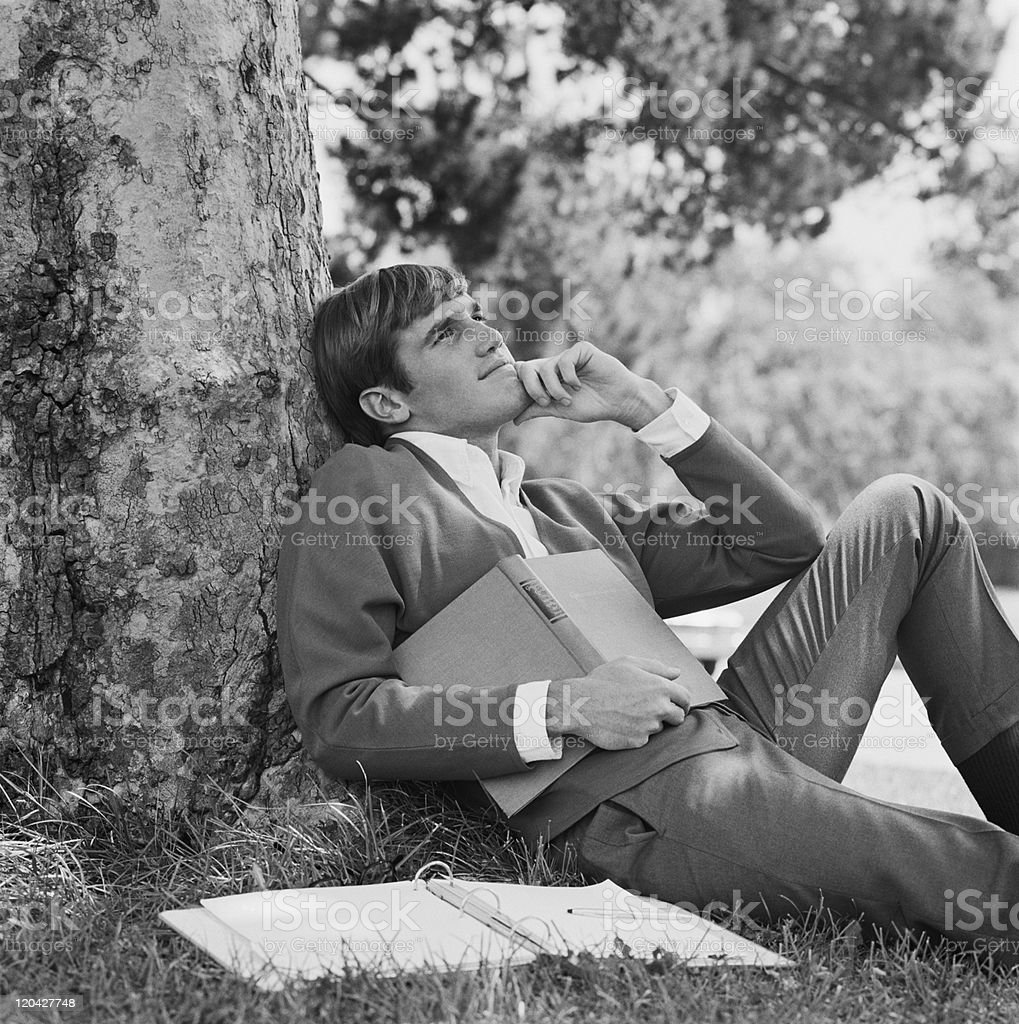Young man leaning against tree, holding book stock photo