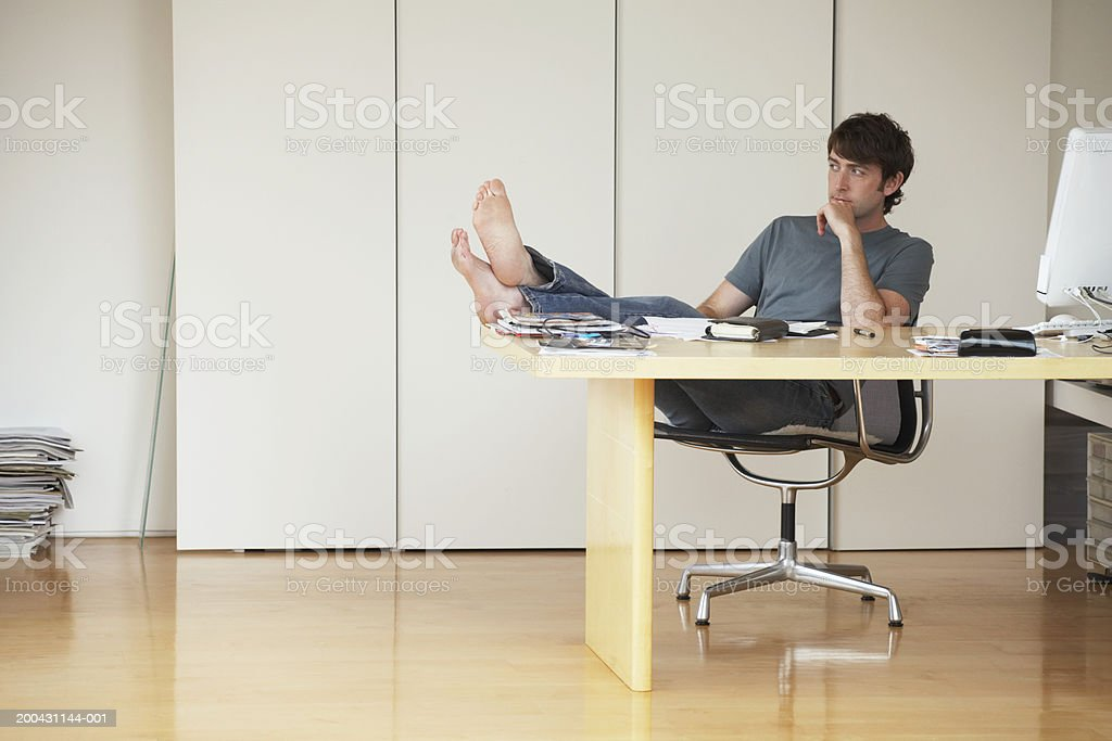 Young man leaning back in chair, feet on desk, resting head on hand royalty-free stock photo