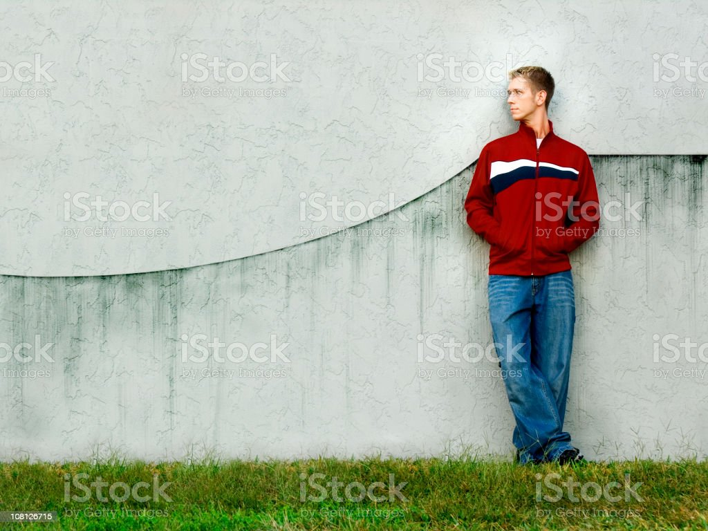 Young Man Leaning on Concrete Wall royalty-free stock photo