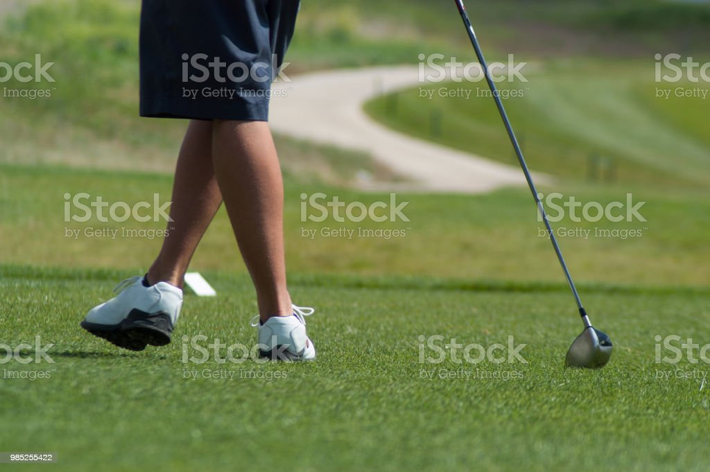 Young man leaning on his golf club on the putting green wearing blue...