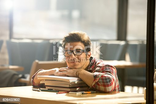 istock Young man leans on stack of books 626402802