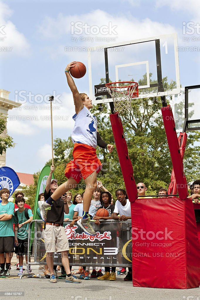 Young Man Leaps High In Outdoor Slam Dunk Contest royalty-free stock photo