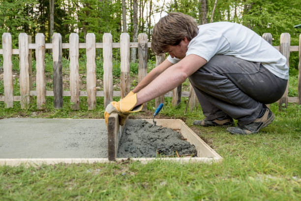 Young man leveling cement in a backyard stock photo