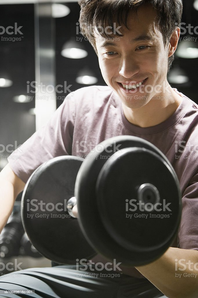 Young man lifting dumb bell in gym, smiling, close-up foto stock royalty-free
