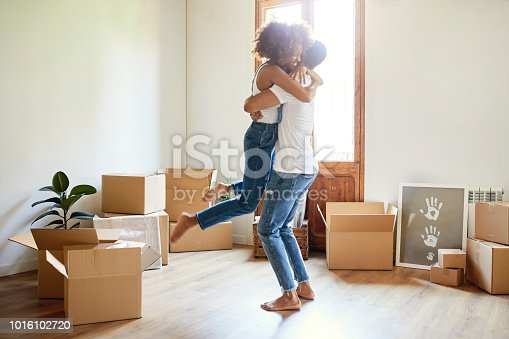 Full length of young man lifting woman in new house. Loving couple is surrounded with cardboard boxes. They are wearing casuals.