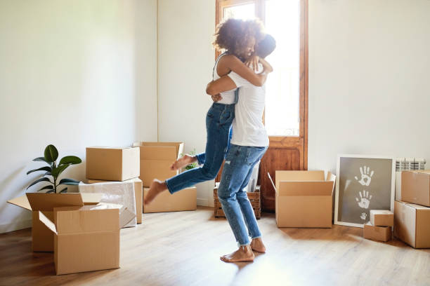 young man lifting woman in new house - house hunting stock photos and pictures