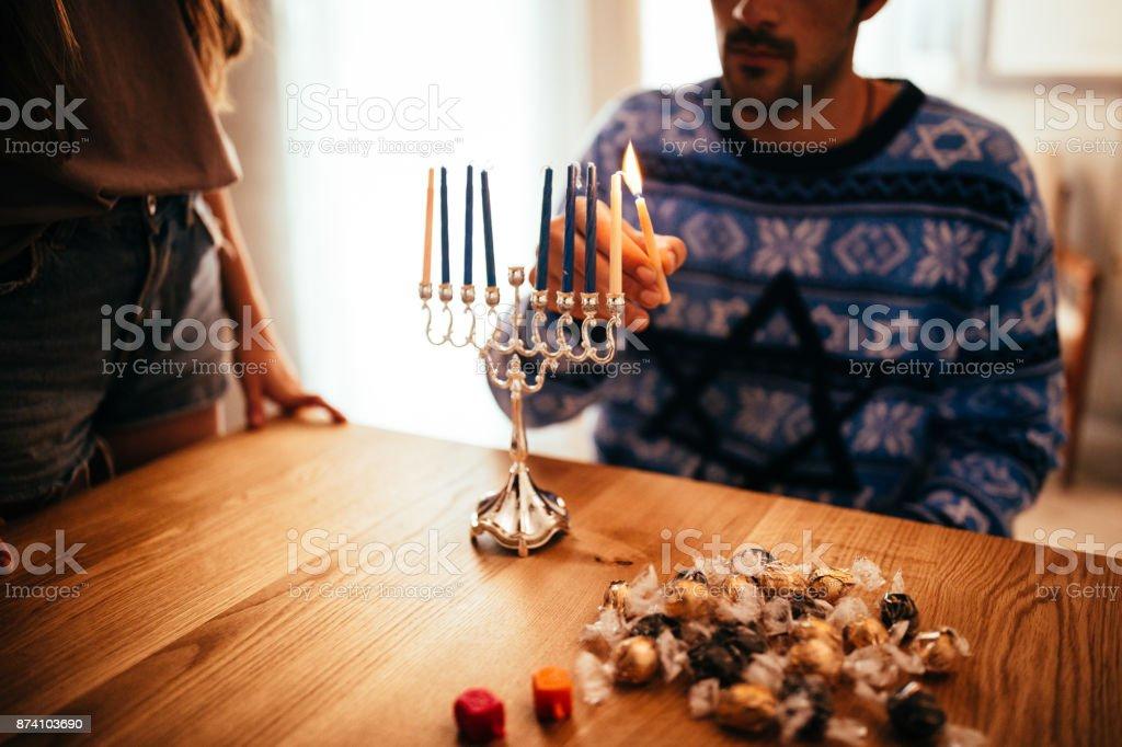 若者 Hannukah の伝統的なユダヤ人本枝の燭台にろうそくを照明 ストックフォト