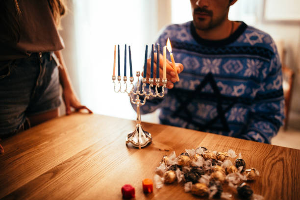 Young man lighting candlesticks on traditional jewish menorah for Hannukah stock photo
