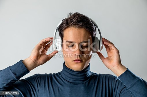 young man listen to the music with wireless headphone