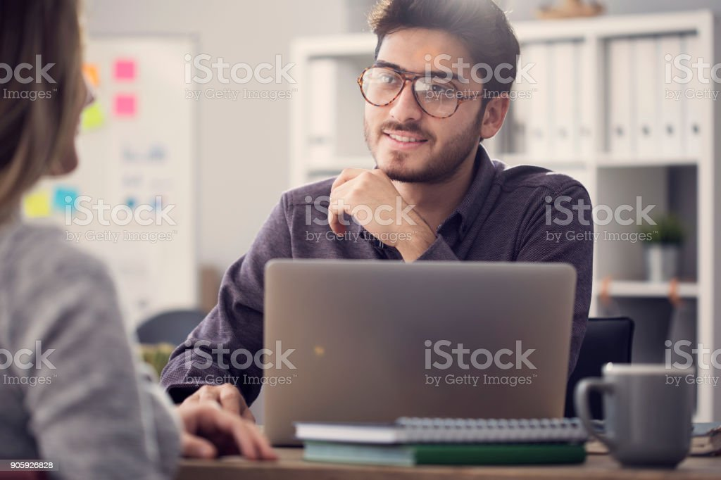 Young man listening a client in the office stock photo