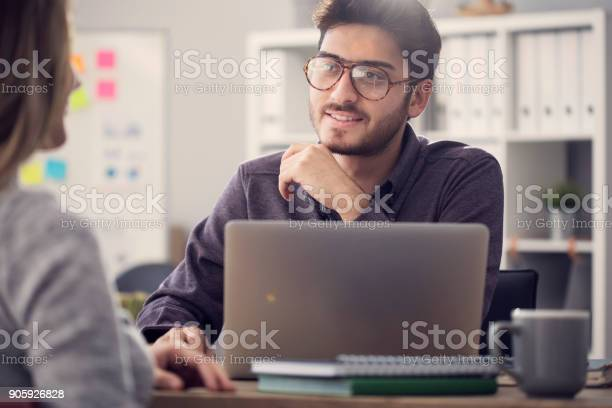 Young Man Listening A Client In The Office Stock Photo - Download Image Now