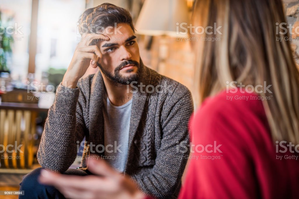 Young man listening to his girlfriend about her problems. stock photo