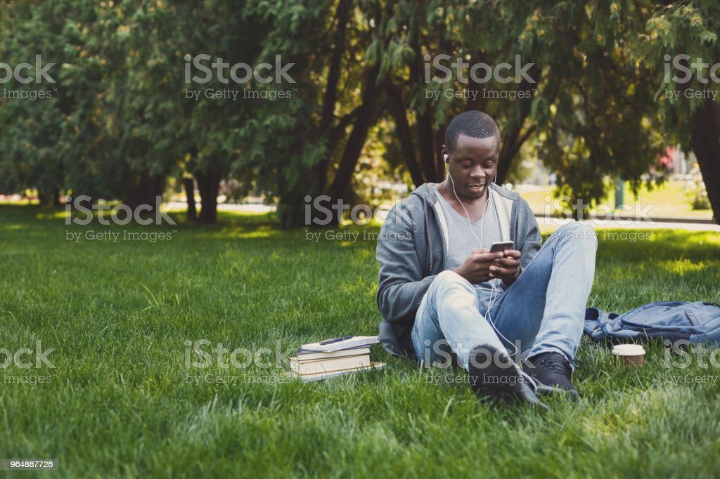 Young man listening to music on grass outdoors royalty-free stock photo