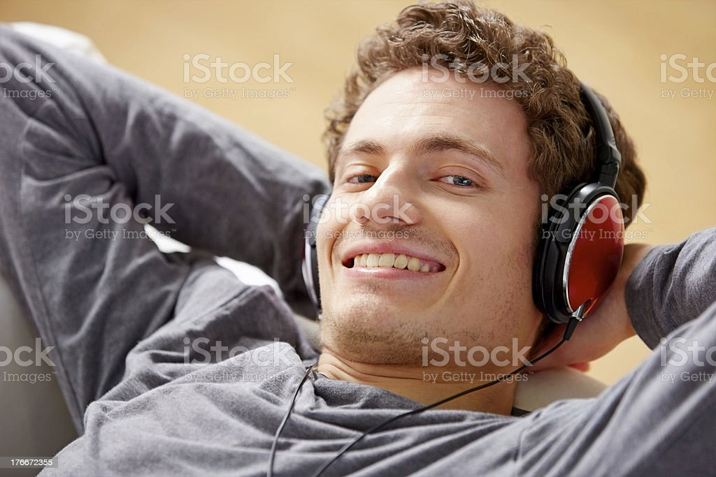 Young man listening to music on headphones royalty-free stock photo
