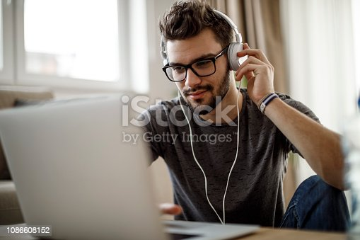 Young man listening to music on laptop at home
