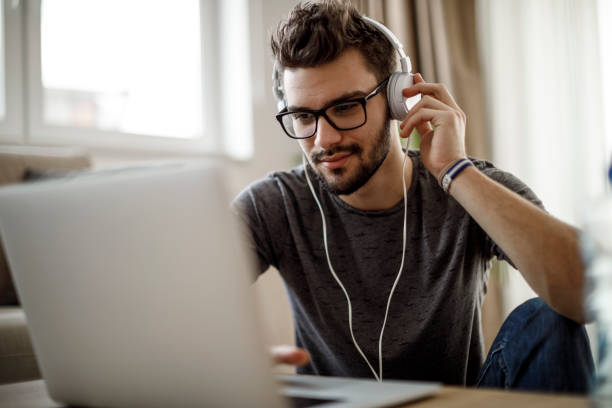 Young man listening to music on laptop at home stock photo